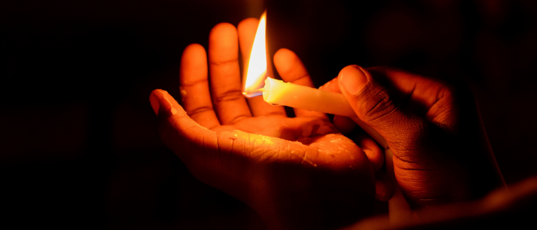 Hands around a burning candle
