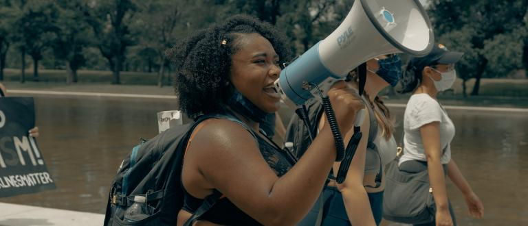 Black woman talking into a megaphone