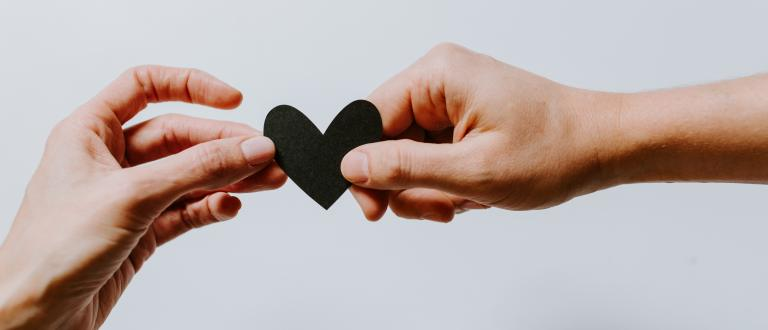 two hands holding paper heart