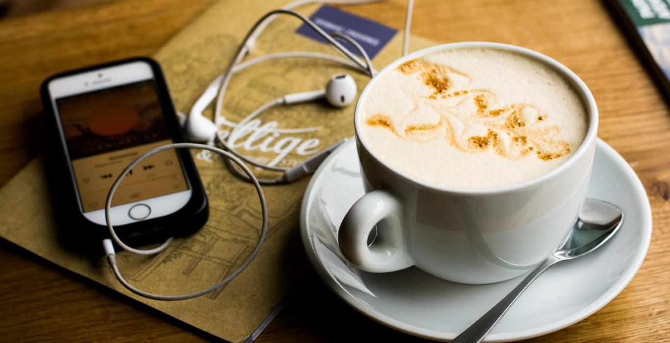 Photo of coffee, phone and earbuds