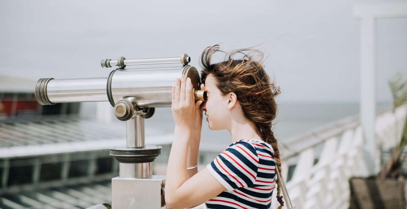 girl looking through large binoculars