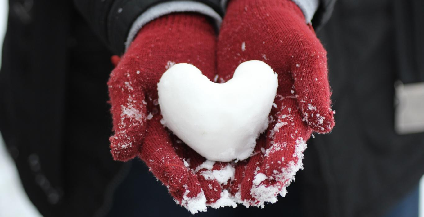 Heart shaped snowball in gloves