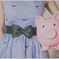 girl in blue dress holding piggy bank